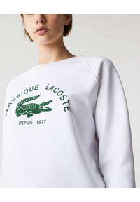 Lacoste - LACOSTE - Biała bluza z logo. Kolor: biały. Materiał: bawełna, polar. Długość rękawa: raglanowy rękaw. Wzór: kolorowy. Styl: klasyczny, elegancki, vintage