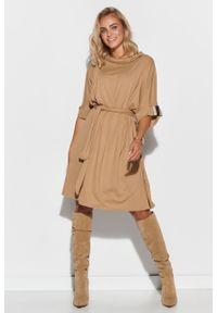 e-margeritka - Sukienka oversize rozkloszowana z paskiem beżowa - 40/42. Typ kołnierza: kołnierzyk stójkowy. Kolor: beżowy. Materiał: dzianina, materiał, skóra, wiskoza, elastan. Wzór: aplikacja. Typ sukienki: oversize. Styl: elegancki