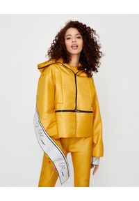 JOANNA MUZYK - Żółta kurtka z logo. Typ kołnierza: kaptur. Kolor: żółty. Materiał: tkanina. Styl: sportowy