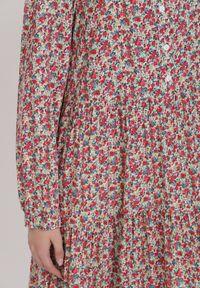 Renee - Różowa Sukienka Rhethelsa. Typ kołnierza: kołnierz z falbankami. Kolor: różowy. Długość rękawa: długi rękaw. Wzór: kwiaty. Długość: midi