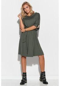 e-margeritka - Sukienka oversize rozkloszowana z paskiem khaki - 40/42. Typ kołnierza: kołnierzyk stójkowy. Kolor: brązowy. Materiał: dzianina, elastan, skóra, wiskoza, materiał. Wzór: aplikacja. Typ sukienki: oversize. Styl: elegancki
