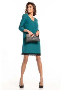 Zielona sukienka wizytowa Tessita w koronkowe wzory