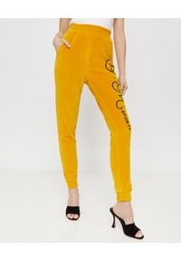 JOANNA MUZYK - Aksamitne spodnie z logo. Stan: podwyższony. Kolor: żółty. Materiał: dresówka. Wzór: aplikacja