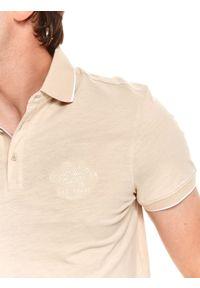 TOP SECRET - T-shirt polo ze strukturalnej dzianiny. Typ kołnierza: polo. Kolor: beżowy. Materiał: dzianina. Długość rękawa: krótki rękaw. Długość: krótkie. Wzór: aplikacja. Styl: klasyczny