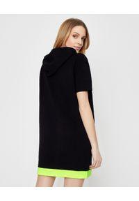 MOSCHINO - Czarna sukienka z kapturem. Typ kołnierza: kaptur. Kolor: czarny. Materiał: bawełna. Typ sukienki: sportowe. Styl: elegancki, sportowy. Długość: mini