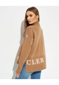 MONCLER - Beżowy sweter z golfem. Typ kołnierza: golf. Kolor: beżowy. Materiał: kaszmir, wełna. Długość rękawa: długi rękaw. Długość: długie. Wzór: nadruk