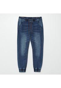 Cropp - Jeansowe joggery z efektem sprania - Granatowy. Kolor: niebieski