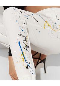 JOANNA MUZYK - Białe spodnie z farbą Iza. Stan: podwyższony. Kolor: biały. Materiał: dresówka. Wzór: aplikacja