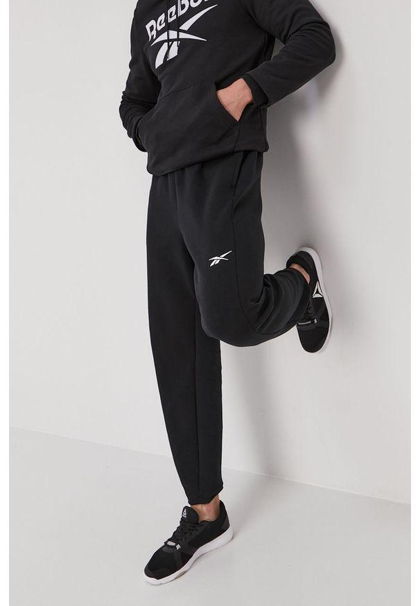 Reebok - Spodnie. Kolor: czarny. Materiał: dzianina, bawełna, poliester, elastan. Wzór: gładki