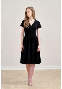 Marie Zélie - Sukienka Larissa czarna krótki rękaw. Typ kołnierza: dekolt kopertowy. Kolor: czarny. Materiał: materiał, bawełna, dzianina, skóra, elastan. Długość rękawa: krótki rękaw. Typ sukienki: kopertowe