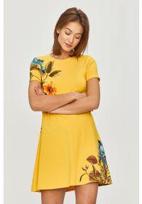 Desigual - Sukienka. Kolor: żółty. Materiał: dzianina. Długość rękawa: krótki rękaw. Wzór: nadruk. Typ sukienki: rozkloszowane