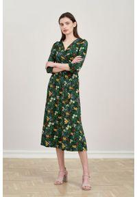 Marie Zélie - Sukienka Rita Lucida zieleń butelkowa. Typ kołnierza: dekolt kopertowy. Materiał: wiskoza, dzianina, materiał, elastan, tkanina. Długość rękawa: krótki rękaw. Typ sukienki: proste, kopertowe