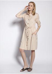 e-margeritka - Sukienka koszulowa na guziki wiązana w talii beżowa - 40. Okazja: na co dzień. Kolor: beżowy. Materiał: tkanina, wiskoza, materiał. Długość rękawa: długi rękaw. Typ sukienki: koszulowe. Styl: casual. Długość: midi