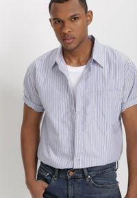 Born2be - Jasnoniebieska Koszula Theisine. Okazja: na co dzień. Kolor: biały. Materiał: tkanina, materiał, jeans. Długość rękawa: krótki rękaw. Długość: krótkie. Wzór: paski. Styl: klasyczny, casual