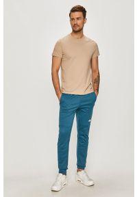 Niebieskie spodnie dresowe The North Face z nadrukiem