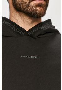 Calvin Klein Jeans - Bluza bawełniana. Okazja: na co dzień. Typ kołnierza: kaptur. Kolor: czarny. Materiał: bawełna. Wzór: nadruk. Styl: casual