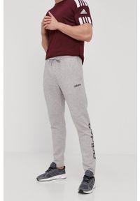 Adidas - Spodnie. Okazja: na co dzień. Kolor: szary. Materiał: dzianina, poliester. Wzór: nadruk. Styl: casual