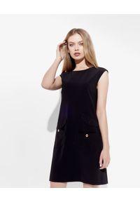 MOSCHINO - Czarna sukienka z guzikami. Kolor: czarny. Materiał: materiał. Typ sukienki: sportowe, z odkrytymi ramionami. Styl: sportowy, klasyczny. Długość: mini