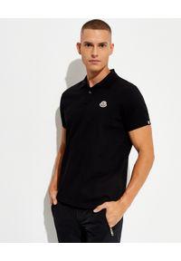 MONCLER - Czarna koszulka polo. Typ kołnierza: polo. Kolor: czarny. Materiał: bawełna. Wzór: aplikacja