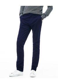 Lacoste - LACOSTE - Granatowe spodnie chino Slim Fit. Kolor: niebieski. Materiał: bawełna, tkanina. Styl: klasyczny