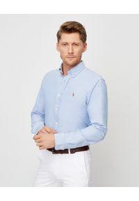 Ralph Lauren - RALPH LAUREN - Niebieska koszula Oxford Regular Fit. Okazja: na spotkanie biznesowe. Typ kołnierza: polo. Kolor: niebieski. Materiał: bawełna. Długość rękawa: długi rękaw. Długość: długie. Wzór: haft, kolorowy. Styl: biznesowy