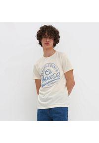 Kremowy t-shirt House z napisami