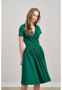 Marie Zélie - Sukienka Larissa ciemnozielona krótki rękaw. Typ kołnierza: dekolt kopertowy. Kolor: zielony. Materiał: bawełna, dzianina, materiał, elastan, skóra. Długość rękawa: krótki rękaw. Typ sukienki: kopertowe