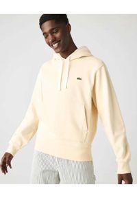 Lacoste - LACOSTE - Beżowa bluza z kapturem Unisex Fit. Typ kołnierza: kaptur. Kolor: beżowy. Materiał: dresówka, bawełna, jeans, prążkowany, polar. Wzór: aplikacja