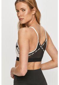 Nike - Biustonosz sportowy. Kolor: biały. Materiał: włókno, skóra, tkanina. Rodzaj stanika: odpinane ramiączka, wyciągane miseczki. Technologia: Dri-Fit (Nike). Wzór: nadruk