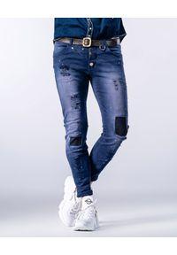 GUNS & TUXEDOS - Granatowe jeansy z łatami Dust Devil. Kolor: niebieski