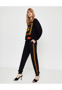 CHAOS BY MARTA BOLIGLOVA - Czarne spodnie dresowe z pomarańczowym logo. Kolor: czarny. Materiał: dresówka. Wzór: nadruk, aplikacja