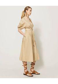 TwinSet - TWINSET - Beżowa midi sukienka z wiązaniem. Kolor: beżowy. Materiał: bawełna. Sezon: wiosna, lato. Typ sukienki: kopertowe. Styl: elegancki. Długość: midi