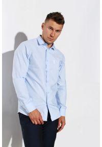 """Koszula Edward Orlovski Błękitna """"White"""". Typ kołnierza: kołnierzyk klasyczny. Kolor: niebieski. Materiał: bawełna, włókno. Długość rękawa: krótki rękaw. Długość: krótkie. Styl: elegancki"""