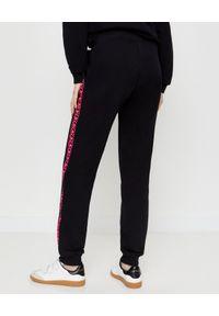 CHAOS BY MARTA BOLIGLOVA - Czarne spodnie dresowe z różowym logo. Kolor: czarny. Materiał: dresówka. Wzór: nadruk, aplikacja