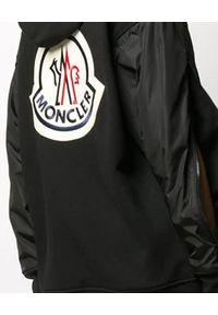 MONCLER - Czarna bluza z logo na plecach. Okazja: na co dzień. Kolor: czarny. Materiał: bawełna, dresówka, nylon, jeans. Długość rękawa: długi rękaw. Długość: długie. Wzór: aplikacja. Sezon: jesień. Styl: klasyczny, casual