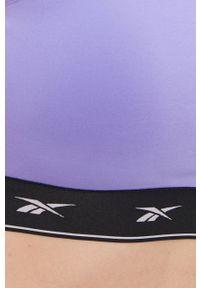 Reebok - Biustonosz sportowy. Kolor: fioletowy. Materiał: skóra. Rodzaj stanika: wyciągane miseczki