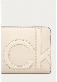 Calvin Klein - Portfel. Kolor: beżowy. Materiał: materiał. Wzór: gładki