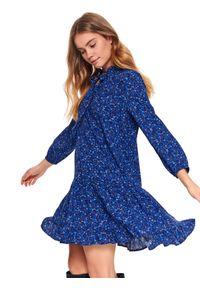 TOP SECRET - Sukienka ze stójką w kwiaty. Typ kołnierza: kołnierzyk stójkowy. Kolor: niebieski. Materiał: materiał. Długość rękawa: długi rękaw. Wzór: kwiaty. Sezon: wiosna. Typ sukienki: rozkloszowane