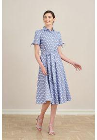 Marie Zélie - Sukienka Ariana lniana błękitna w białe grochy. Kolor: niebieski, biały, wielokolorowy. Materiał: len. Długość rękawa: krótki rękaw. Wzór: grochy. Sezon: lato. Typ sukienki: szmizjerki, trapezowe