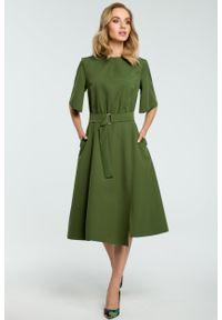 e-margeritka - Elegancka sukienka do biura midi z paskiem - ciemna zieleń, l. Okazja: na spotkanie biznesowe, do pracy. Kolor: różowy, brązowy. Materiał: tkanina, elastan, poliester, włókno, materiał. Wzór: kolorowy, jednolity. Sezon: jesień, zima. Typ sukienki: kopertowe, proste, dopasowane, rozkloszowane. Styl: elegancki, biznesowy. Długość: midi