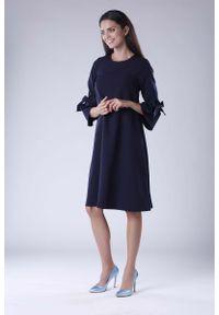 Nommo - Granatowa Trapezowa Sukienka Wizytowa z Efektownym Rękawem. Kolor: niebieski. Materiał: wiskoza, poliester. Typ sukienki: trapezowe. Styl: wizytowy