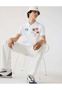 Lacoste - LACOSTE - Biała koszulka polo z naszywkami Regular fit. Typ kołnierza: polo. Kolor: biały. Materiał: prążkowany, bawełna. Wzór: aplikacja