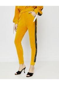 JOANNA MUZYK - Spodnie dresowe z taśmami. Kolor: żółty. Materiał: dresówka. Wzór: aplikacja
