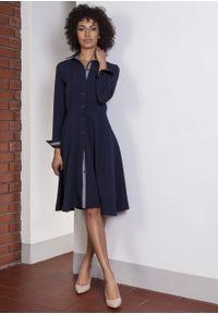 e-margeritka - Sukienka rozkloszowana taliowana granat - 40. Okazja: do pracy. Materiał: tkanina, poliester, materiał, elastan. Sezon: lato, wiosna. Typ sukienki: proste, rozkloszowane. Styl: elegancki