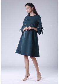 Nommo - Zielona Trapezowa Sukienka Wizytowa z Efektownym Rękawem. Kolor: zielony. Materiał: wiskoza, poliester. Typ sukienki: trapezowe. Styl: wizytowy