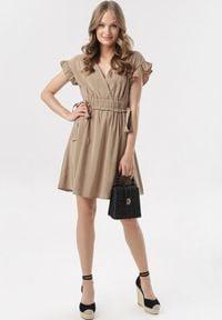 Born2be - Beżowa Sukienka Corraenelle. Typ kołnierza: kołnierz z falbankami. Kolor: beżowy. Długość rękawa: krótki rękaw. Typ sukienki: kopertowe. Długość: mini