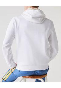 Lacoste - LACOSTE - Biała bluza z kapturem. Okazja: na co dzień. Typ kołnierza: kaptur. Kolor: biały. Materiał: materiał, jeans. Długość rękawa: długi rękaw. Długość: długie. Wzór: aplikacja. Styl: casual, klasyczny