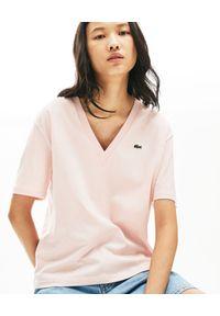 Lacoste - LACOSTE - Różowy t-shirt z haftem w serek. Typ kołnierza: dekolt w serek. Kolor: różowy, wielokolorowy, fioletowy. Materiał: bawełna, jeans, prążkowany. Wzór: haft