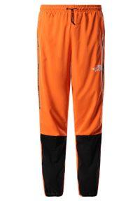 Pomarańczowe spodnie dresowe The North Face z aplikacjami