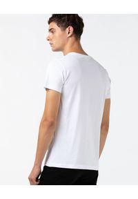 Lacoste - LACOSTE - Biały t-shirt z nadrukiem logo Regular Fit. Kolor: biały. Materiał: bawełna, jeans. Wzór: nadruk. Styl: sportowy, klasyczny